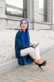 Wspaniała dziewczyna z hidżabem siedzi na zewnątrz