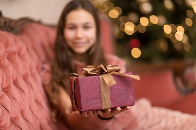 Wspaniała dziewczyna z świątecznym prezentem w stylowym wnętrzu.