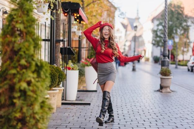 Wspaniała dziewczynka kaukaski w skórzanych czarnych butach, stojąca ze skrzyżowanymi nogami na chodniku