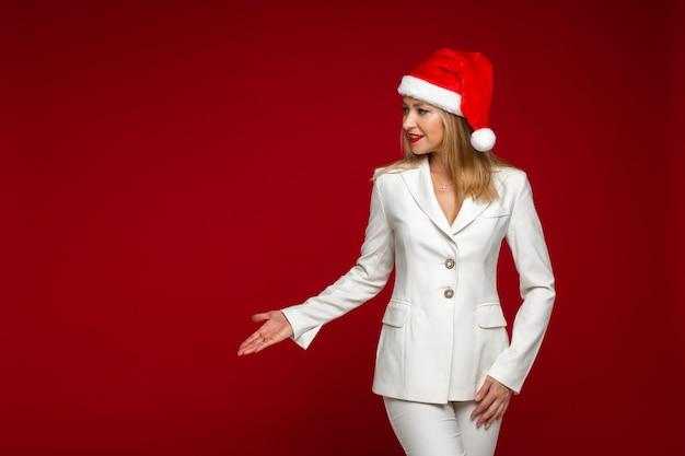 Wspaniała elegancka blondynka kaukaska kobieta w białym garniturze i santa hat pokazując miejsce na czerwoną ścianę. koncepcja bożego narodzenia.