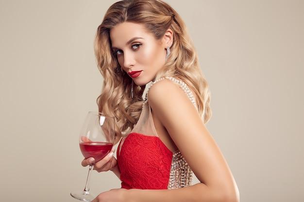 Wspaniała elegancka blondynki kobieta jest ubranym mody czerwoną suknię