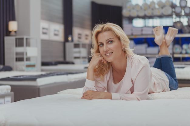Wspaniała elegancka dojrzała kobieta robi zakupy dla nowego łóżka ortopedycznego
