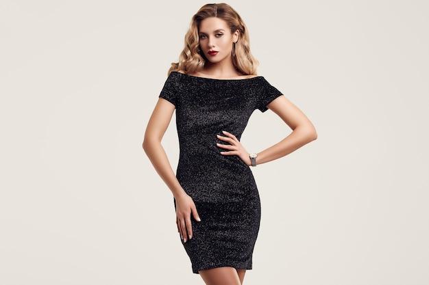 Wspaniała elegancka zmysłowa blondynki kobieta jest ubranym modną czarną suknię