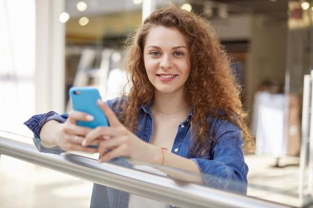 Wspaniała fotografia portretowa przedstawiająca osobę stojącą w pomieszczeniu, patrz bezpośrednio w ramkę i uśmiechaj się. na twarzy niebieskie oczy są bez makijażu