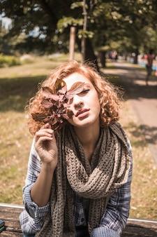 Wspaniała imbirowa kobieta z jesień liśćmi w parku