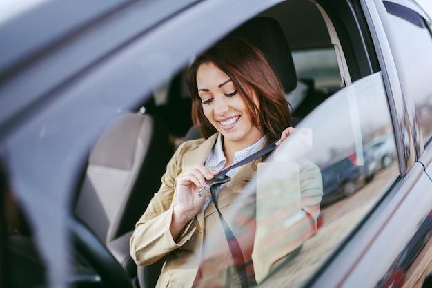 Wspaniała kaukaska brunetka ubrana elegancko na co dzień siedzi w samochodzie i zapinając pas bezpieczeństwa.