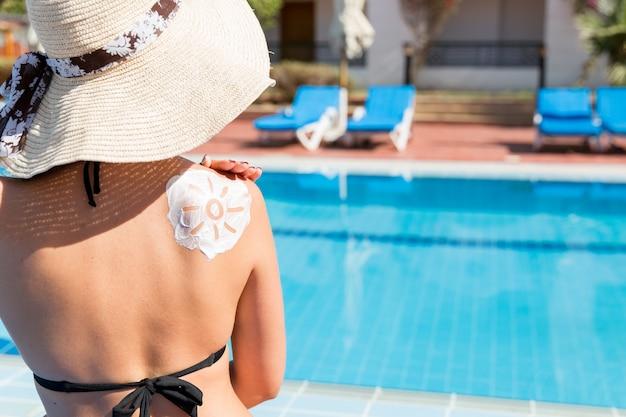Wspaniała kobieta ma na ramieniu przy basenie krem z filtrem przeciwsłonecznym w kształcie słońca. współczynnik ochrony przeciwsłonecznej na wakacjach, koncepcja.