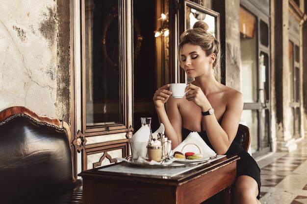 Wspaniała kobieta ma na sobie czarną sukienkę we włoskiej kawiarni w stylu vintage