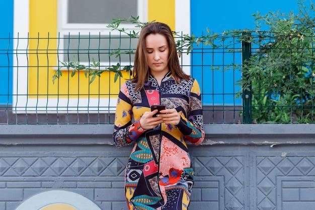 Wspaniała kobieta opiera na ścianie i trzyma telefon w kolorowej sukni na ulicie
