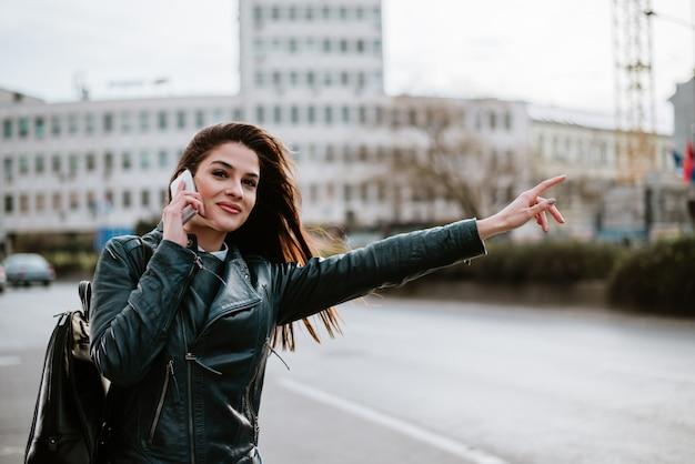 Wspaniała kobieta opowiada na miasto ulicie, łapie taxi.
