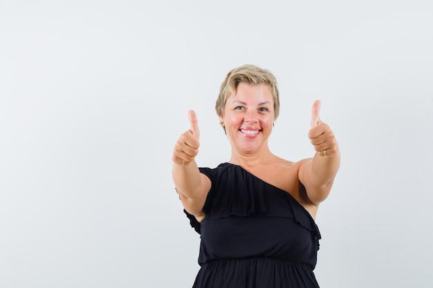 Wspaniała kobieta pokazując kciuk w czarnej bluzce i patrząc zadowolony. przedni widok.