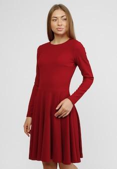 Wspaniała kobieta. portret pięknej uśmiechniętej młodej kobiety stojącej w ślicznej czerwonej sukience na białym tle na białym tle w pełnej długości. koncepcja sukienek reklamowych do sklepu.
