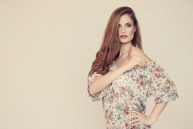 Wspaniała kobieta pozuje z kwiecistą suknią, mody pojęcie