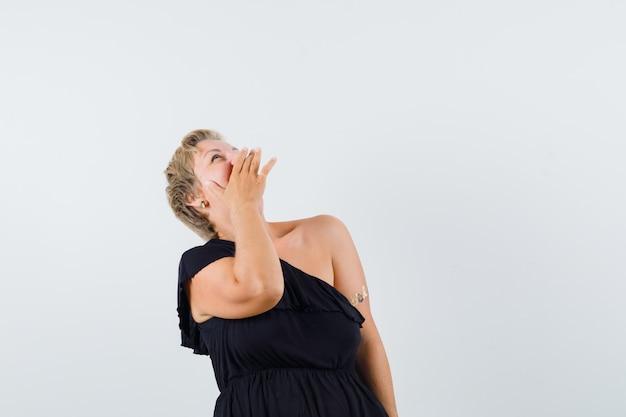 Wspaniała kobieta śmiejąca się, patrząc w czarną bluzkę i patrząc wesoło. przedni widok. miejsce na tekst