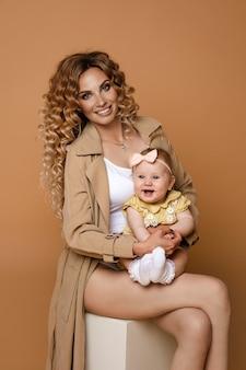 Wspaniała kobieta w beżowym rowie z córeczką i białym topem, trzymająca w ramionach śliczną córeczkę, siedzącą na białym tle na tle brzoskwini.