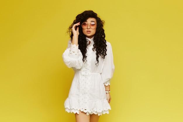 Wspaniała kobieta w białej sukni z okularami przeciwsłonecznymi
