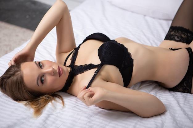 Wspaniała kobieta w czarnej koronkowej bieliźnie leżącej na dużym łóżku