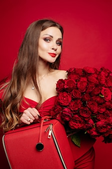 Wspaniała kobieta w czerwonej sukience utrzymanie bukiet róż