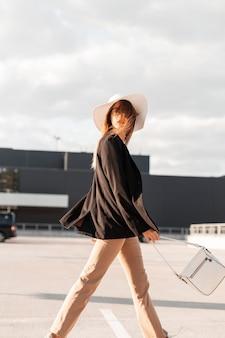 Wspaniała kobieta w modzie słomkowy kapelusz w eleganckie stylowe ubrania z modną torbą idzie na asfalt przeciw błękitnemu słonecznemu niebu. stylowa dziewczyna w ubraniach młodzieżowych w mieście. modne ubrania biznesowe dla kobiet.