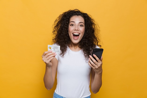Wspaniała kobieta w wieku 20 lat nosząca zwykłe ubrania, trzymająca telefon komórkowy i kartę kredytową na żółto