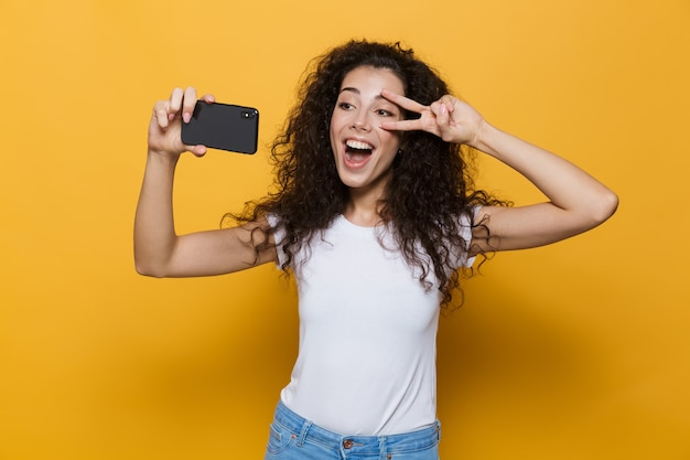 Wspaniała kobieta w wieku 20 lat z kręconymi włosami, trzymająca smartfona i robiąca zdjęcie selfie na żółto