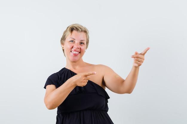 Wspaniała kobieta wskazuje na bok w czarnej bluzce