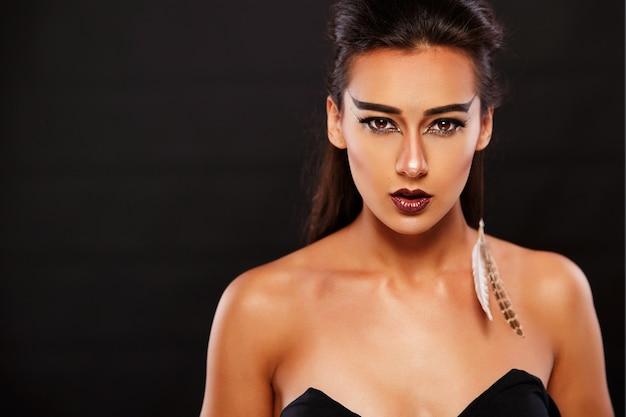 Wspaniała kobieta wygląda jak strzelec z ciemnym makijażem i piórami w uszach