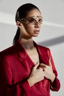 Wspaniała kobieta z biżuterią i w czerwonej kurtce gestykuluje rękami na jasnym tle