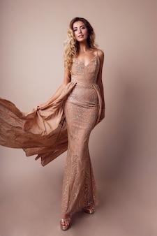 Wspaniała kobieta z blond falowanymi włosami na sobie elegancką beżową sukienkę