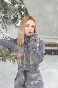 Wspaniała kobieta z długimi włosami pozuje w lesie w śnieżną pogodę