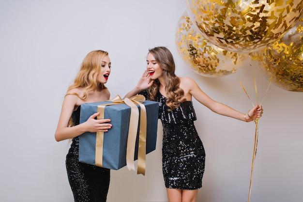 Wspaniała kobieta z elegancką fryzurą trzymająca duży prezent z zaskoczonym wyrazem twarzy. wewnątrz zdjęcie dwóch ładnych dziewczyn bawiących się podczas uroczystości i pozowania