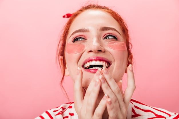 Wspaniała kobieta z łatami na oku, śmiejąc się na różowym tle. szczęśliwa imbirowa dziewczynka kaukaski robi zabieg pielęgnacji skóry.