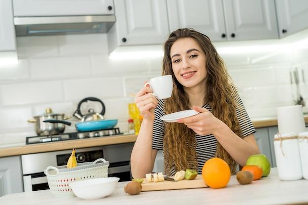 Wspaniała kobieta zrelaksować się rano w kuchni i pić cieszyć się kawą. wygodny wypoczynek w domu.