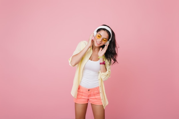 Wspaniała latynoska kobieta w modnym zegarku słuchania muzyki z zamkniętymi oczami. kryty portret niesamowitej latynoskiej modelki w różowych szortach korzystających z piosenki