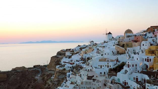 Wspaniała malownicza wioska oia na wyspie santorini o zachodzie słońca, grecja