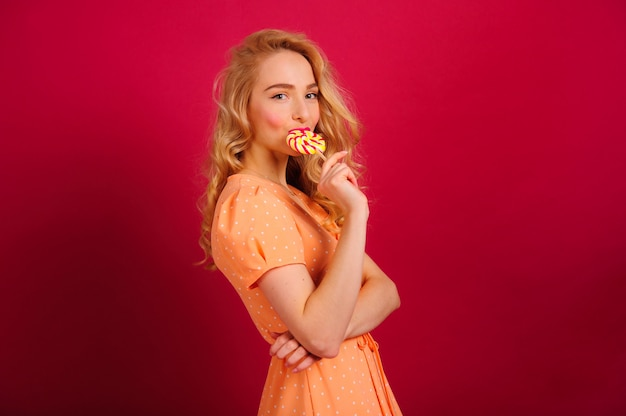 Wspaniała młoda blondynka pozuje na jaskrawej ścianie