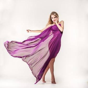 Wspaniała młoda blondynka z purpurowym jedwabiem na szaro