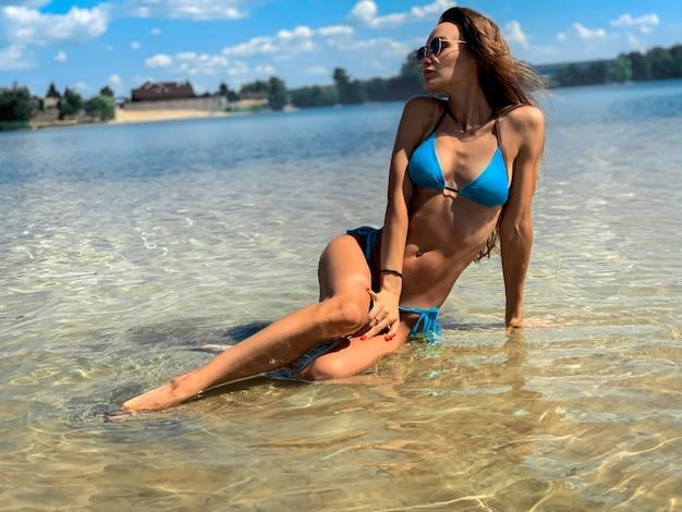 Wspaniała młoda brunetka dama w niebieskim stroju kąpielowym pozowanie na plaży w upalny letni dzień