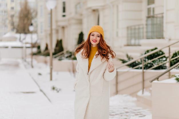 Wspaniała młoda dama pozuje z uśmiechem w styczniu. zimowy portret roześmianej dziewczyny imbiru.