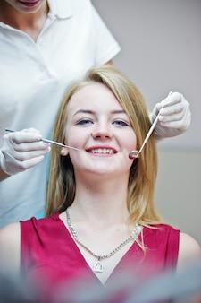 Wspaniała młoda dentystaka sprawdzająca zęby pacjenta w specjalnie wyposażonej szafce.