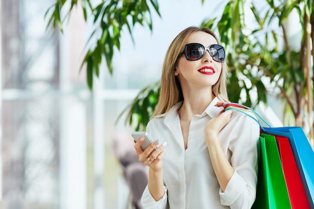 Wspaniała młoda dziewczyna z jasnobrązowymi włosami i czerwonymi ustami, ubrana w białą bluzkę i stojąca z kolorowymi torbami na zakupy, trzymając telefon komórkowy, koncepcja zakupów, kopia przestrzeń.