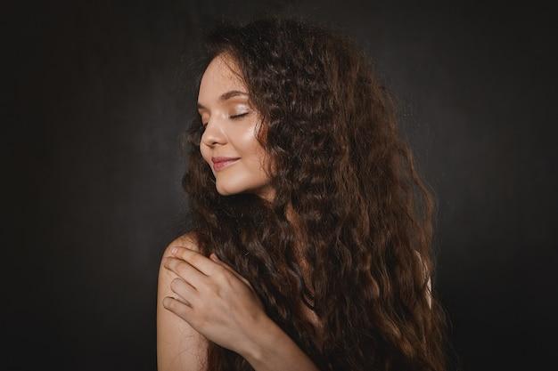Wspaniała młoda europejska modelka o schludnym makijażu i świecącej skórze, z rozpuszczonymi pięknymi ciemnymi włosami, odwracająca wzrok z radosnym uśmiechem, z zamkniętymi oczami