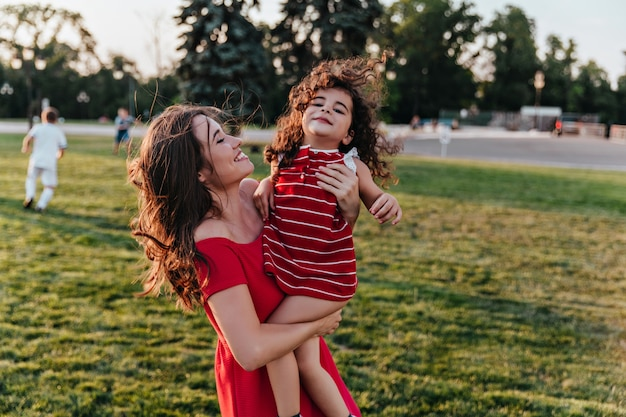 Wspaniała młoda kobieta niosąca córkę i uśmiechnięta. urocza dama patrzy z miłością na kręcone dziecko.