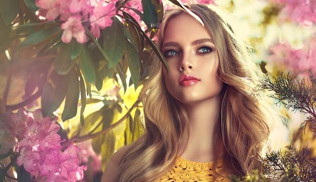 Wspaniała młoda kobieta otoczona kwitnącymi drzewami kwiatowymi delikatny makijaż różana szminka i swobodnie leżące loki 0f długie włosy wiosenny styl wiosenny rozkwit i rozkwit młodości