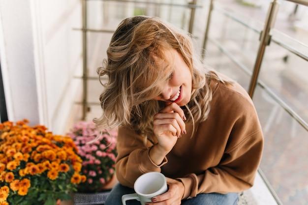 Wspaniała młoda kobieta pije kawę na tarasie. cieszę się, że kaukaski dziewczyna siedzi obok pomarańczowych kwiatów z uśmiechem.