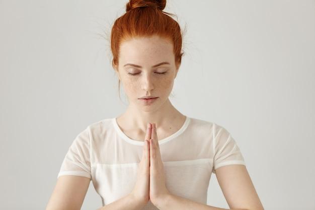 Wspaniała młoda kobieta rasy białej ubrana w rude włosy w kok, trzymając się za ręce w namaste