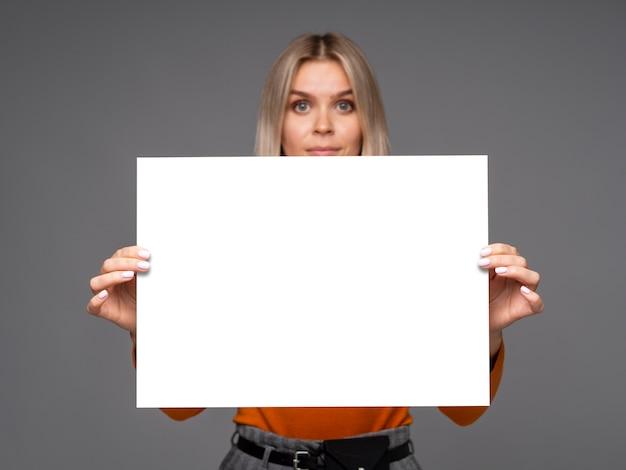 Wspaniała młoda kobieta trzyma arkusz białego papieru