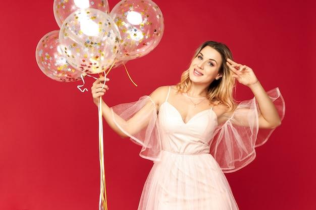 Wspaniała młoda kobieta ubrana w sukienkę bez ramiączek z niskim dekoltem obchodzi urodziny