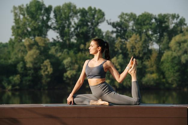 Wspaniała młoda kobieta uprawiająca jogę na świeżym powietrzu w pięknym miejscu nad rzeką