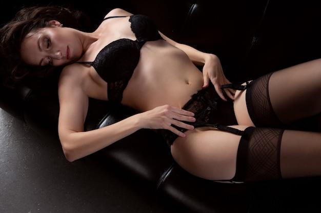 Wspaniała młoda kobieta w czarnej koronkowej bieliźnie leży na kanapie